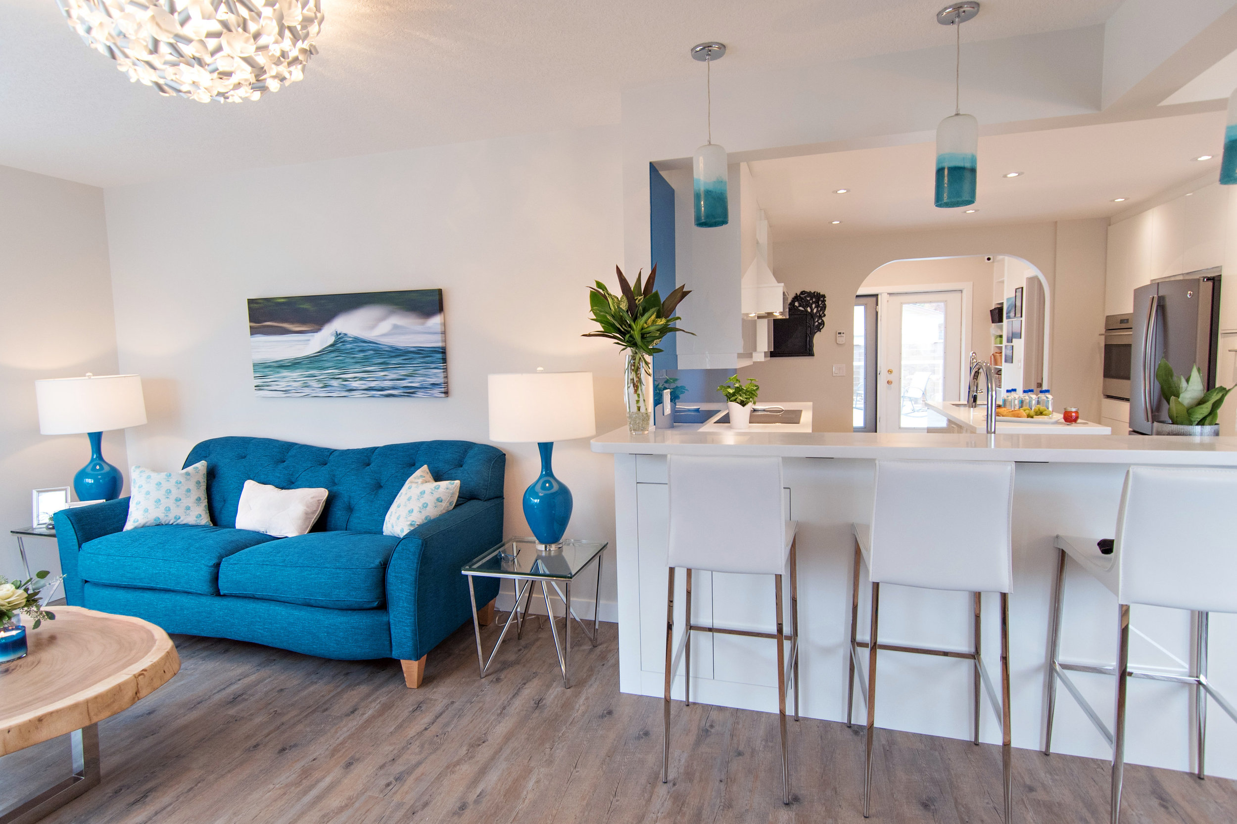 living room with a blue sofa, vinyl plank floor, white bar stools, pendant lighting, Interior Designs By Adrienne , Cranbrook BC