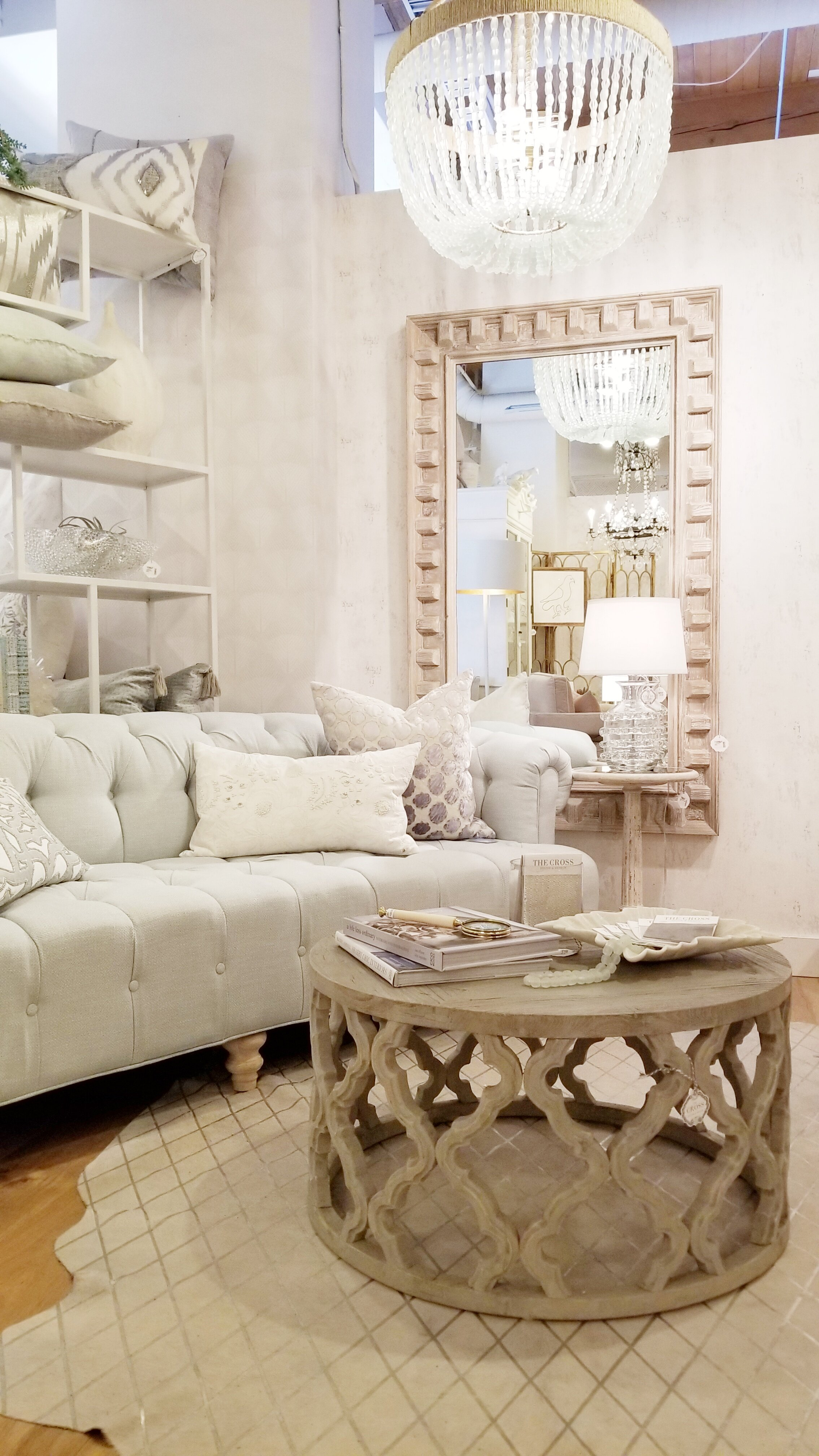 interior-designs-by-adrienne-cranbrook-bc-button-tufted-sofa-mirror-with-wood-frame-beaded-chandelier-the-cross-decor-&-design