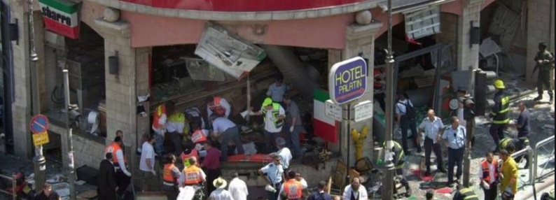 Rescue and paramedic teams work at the site of the Sbarro Restaurant bombing in Downtown Jerusalem on August 9, 2001, which killed 15