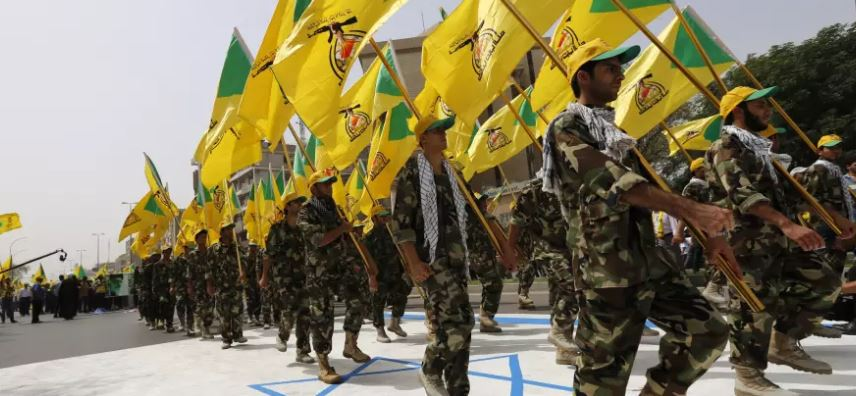 Members of the Iranian-backed group Kataib Hezbollah wave the party's flags as they walk along a street painted in the colors of the Israeli flag in Baghdad. Kataib Hezbollah may have been the target of last night's airstrikes in Syria. (Credit: Thaier al-Sudani, Reuters)