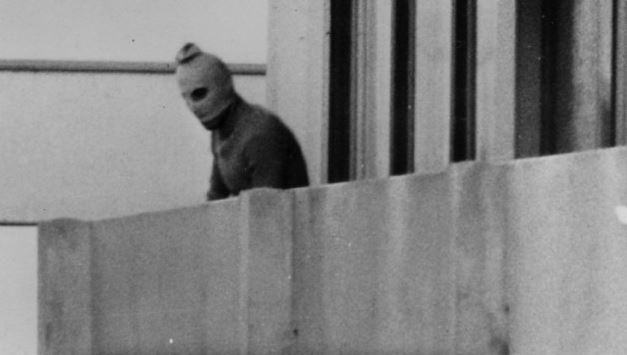 A member of Black September looks over the balcony of one of the Israeli apartments in the Olympic village in Munich, September 5, 1972. (Credit: Getty Images)