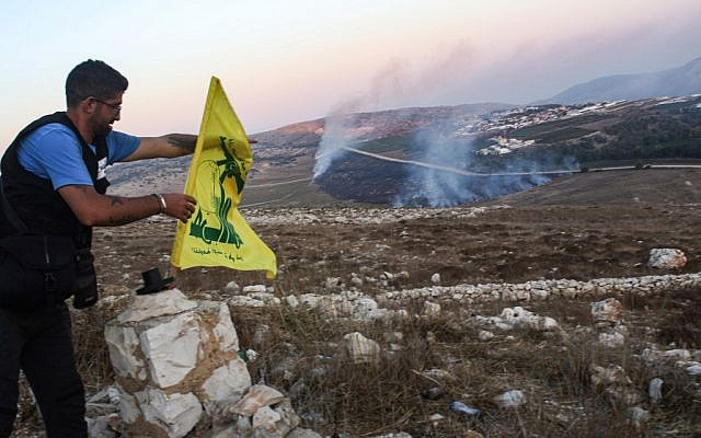 A man fixes a Hezbollah flag at the 'Garden of Iran' Park in the Lebanese village of Maroun al-Ras on September 1 as fires blaze following an exchange of fire with Israel. (Credit: Mahmoud Zayyat, AFP)