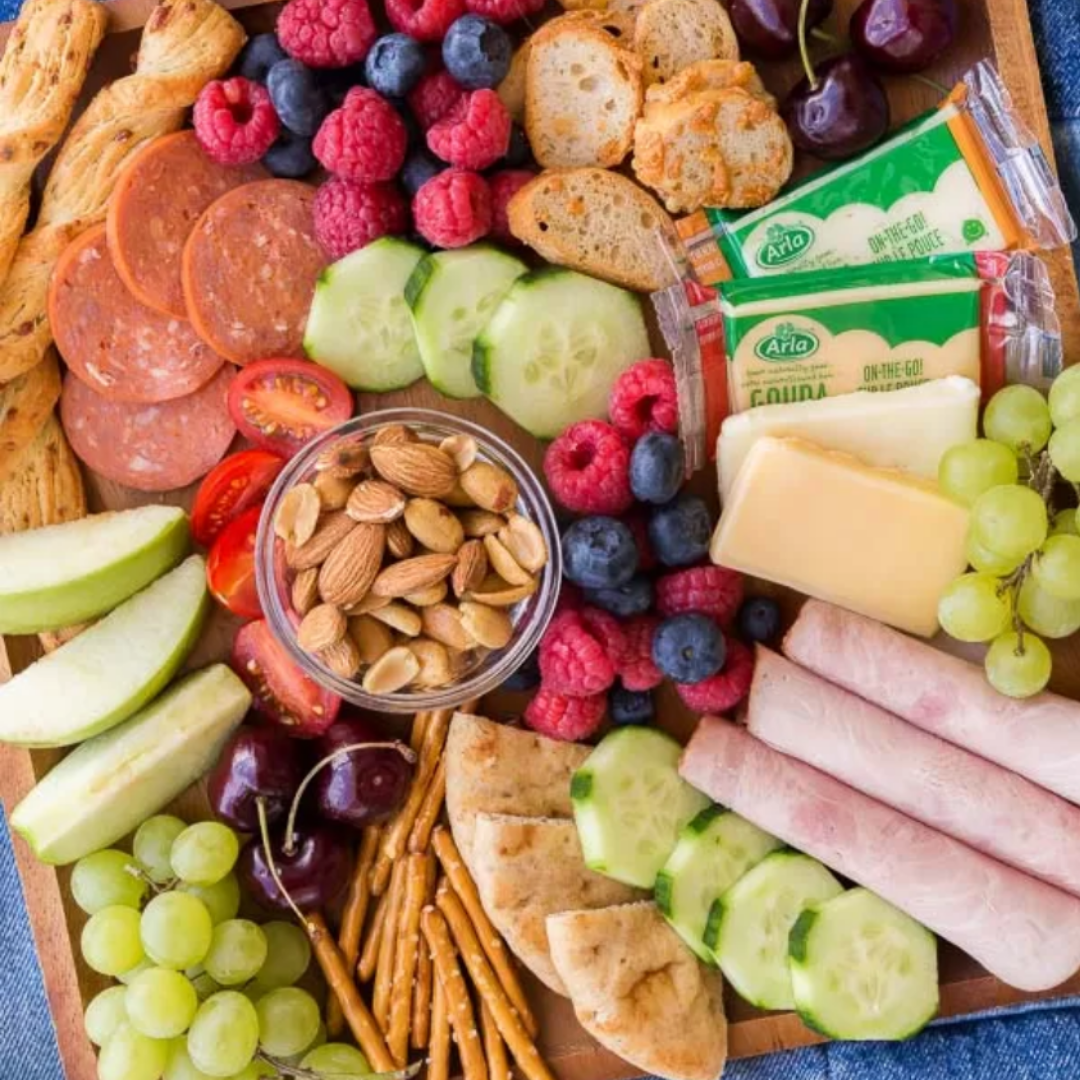 Kid-Friendly Snack Board - Who doesn't love charcuterie? Combine deli-meats and sausage, cheeses, fruit and veggies, and crackers in a couple of reusable containers and voila! The perfect picnic lunch. Very minimal mess, and whatever your kids don't eat can be brought back home and packed the next day in their lunches.Get the inspiration>>
