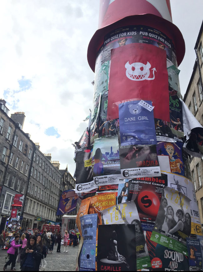 One of the large pillars on The Royal Mile with a Dani Girl poster soon to be covered up by hundreds of other posters.
