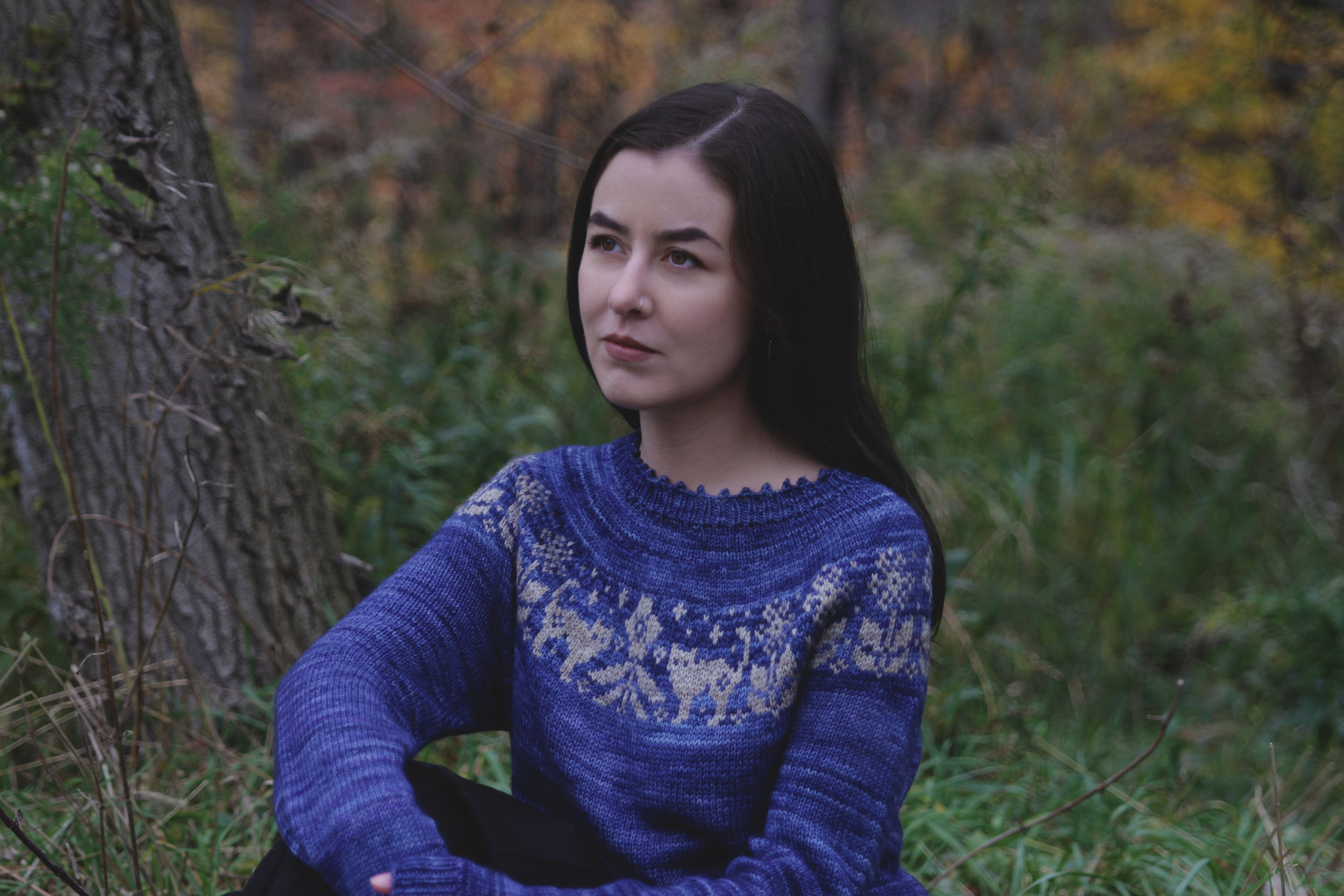 Half Japanese woman wearing a hand knit sweater sitting in the grass.