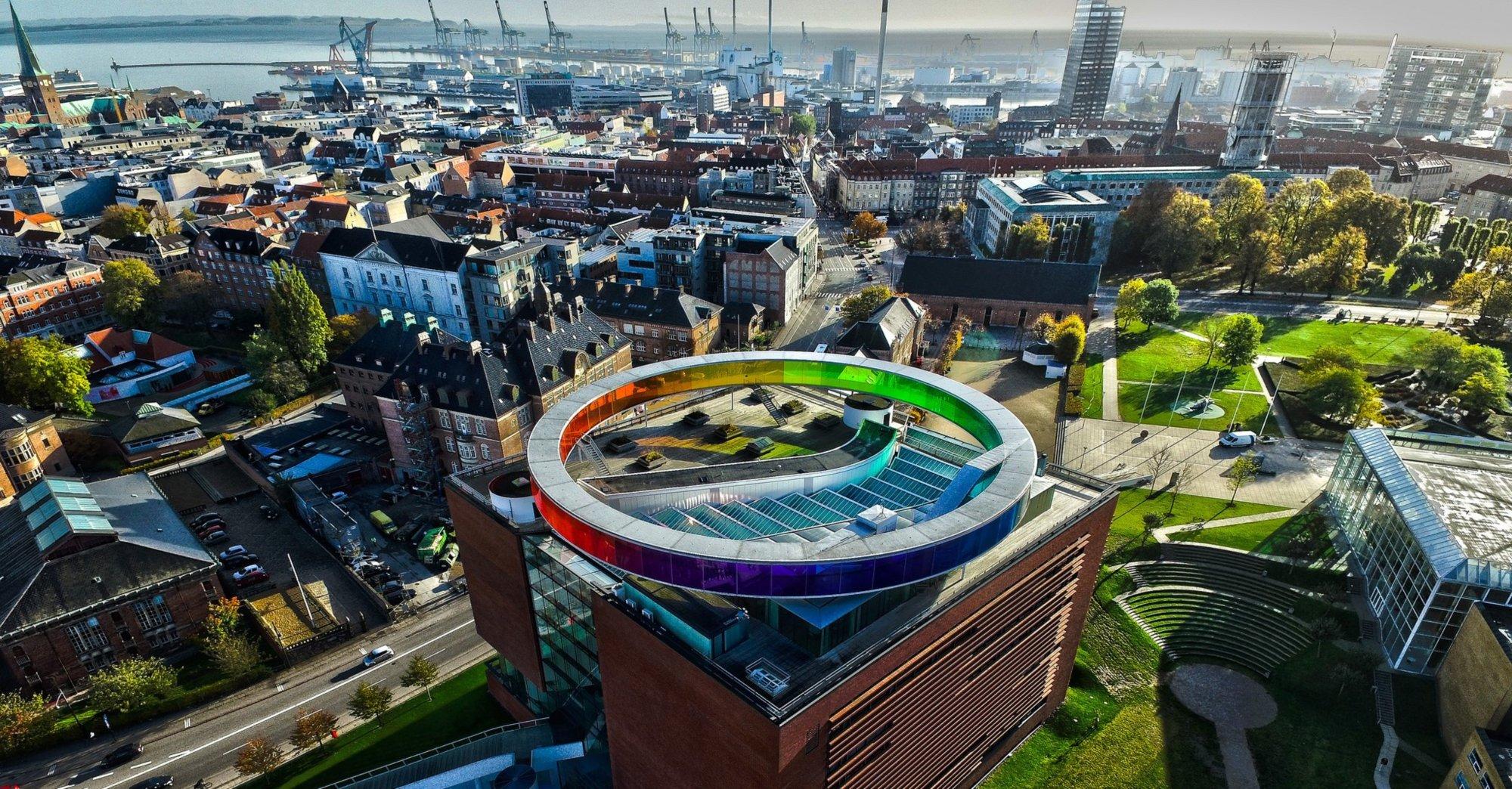 """Dronebilde over Aarhus by med AROS Kunstmuseum i sentrum, med kunstverket """"Your Rainbow Panorama"""" av den verdenskjente Islandsk-Danske kunstneren Olafur Eliasson   Foto:  SmartDronesAarhus"""