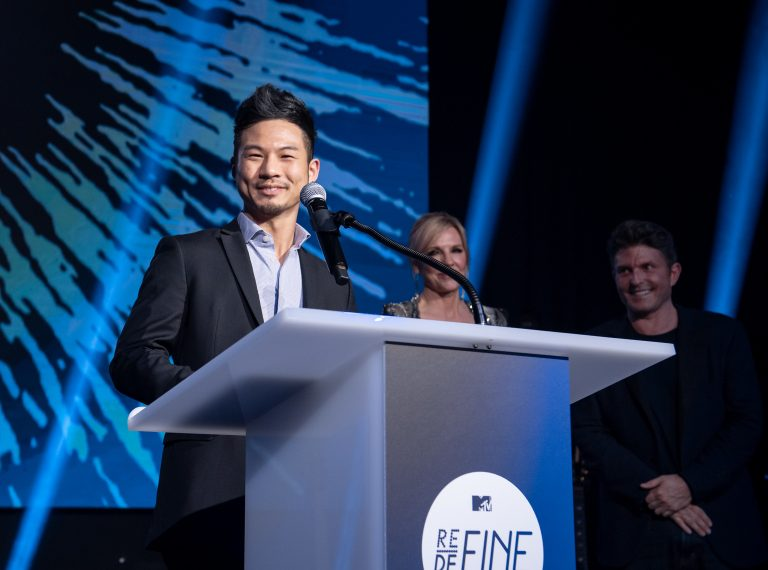 Shohei Katayama (Carnegie Mellon University), winner of the inaugural MTV RE:DEFINE Award in 2019, accepts his award as Joyce Goss and Kenny Goss look on.