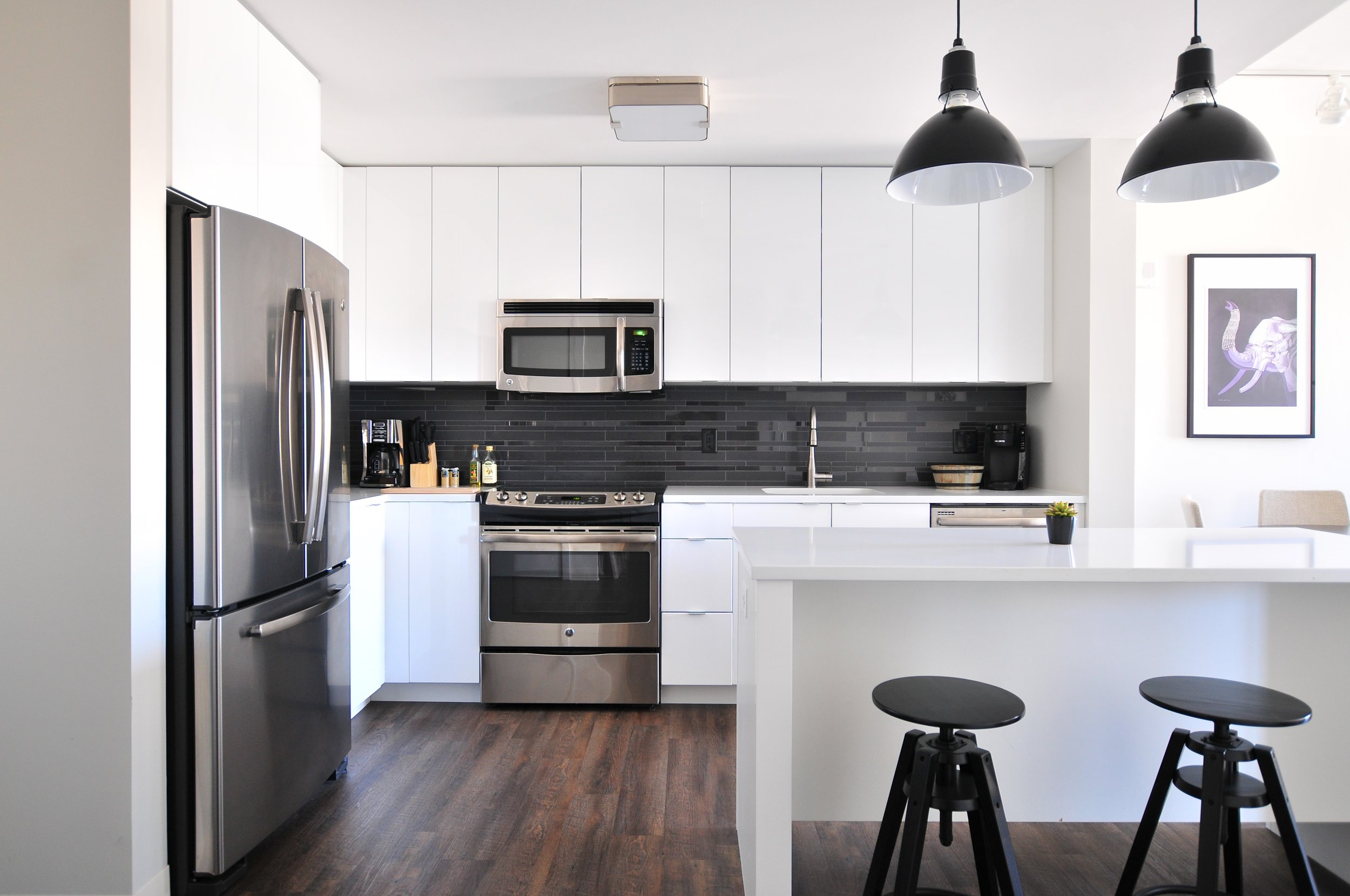 Simple clean lines accent this kitchen. Flat panel white cabinet doors without handles create a sleek look. Black accent tile for the backsplash combined with other black accents in the kitchen (light fixtures and stools) create a beautiful contemporary look.