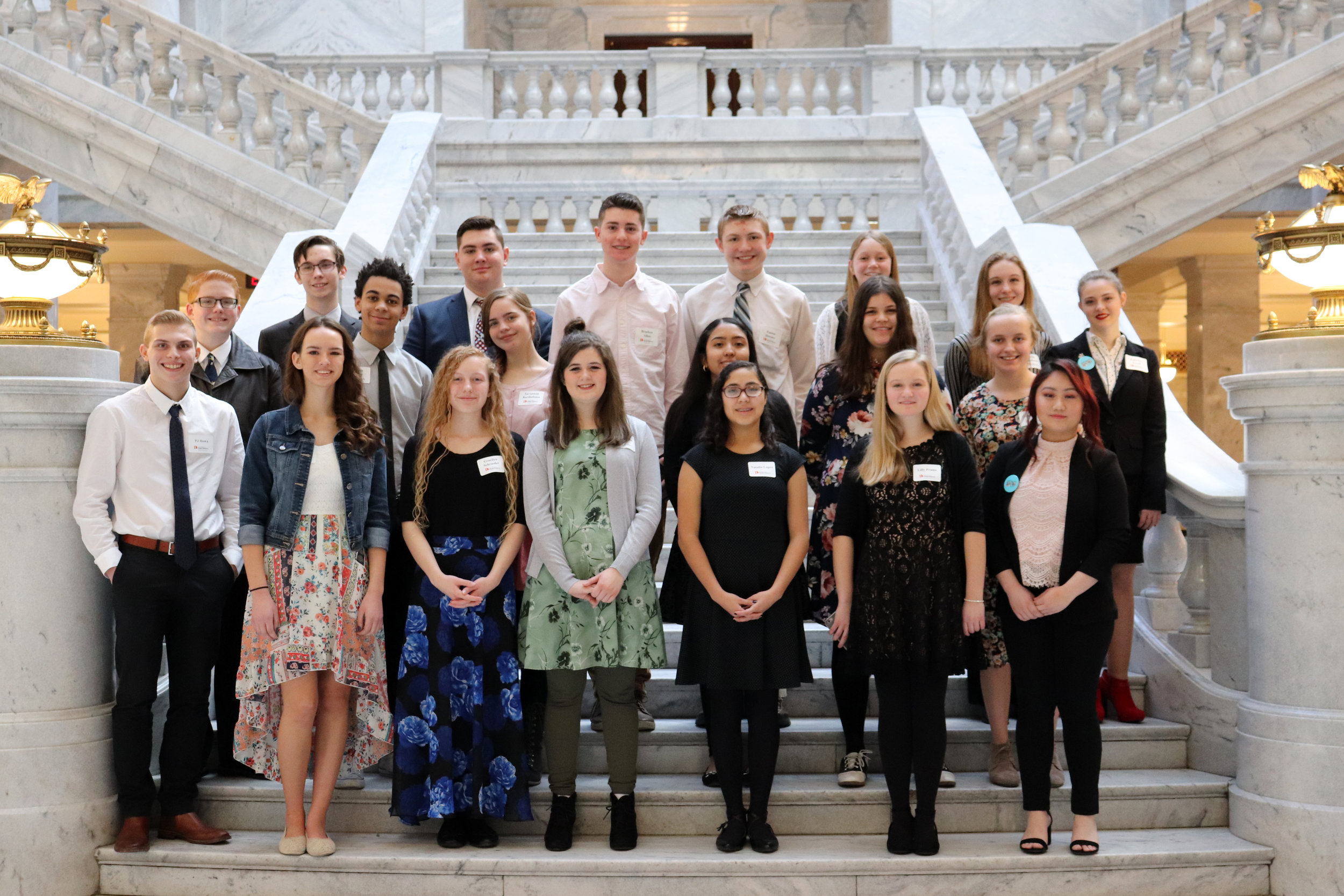On the interior steps of the Capitol, students gather for a group photo.
