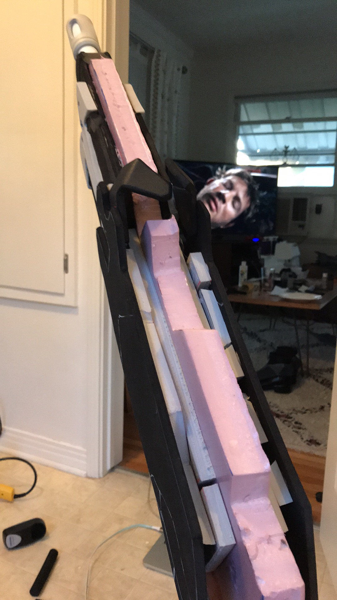 The gun was a layer of pink insulation foam with layers of various densities of EVA foam on top. This ended up making the gun thicker than it is in-game, but I realized too late! (And yep that's  Van Helsing  in the background.)