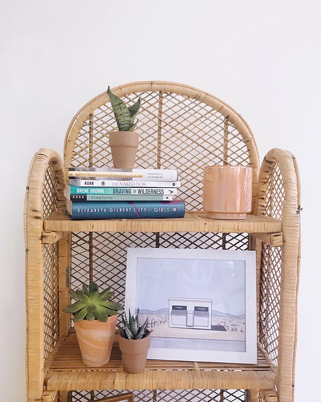 Finally putting my dreamy rattan shelf from @wreckingballcollective to use! Aaaand it's a perfect fit for my 8x10 Prada Marfa print! ✨ Also DYING to read City of Girls (bottom book on the shelf) has anyone else read it yet?! ...PS- grab this print on my online shop for only $12 💛🌵