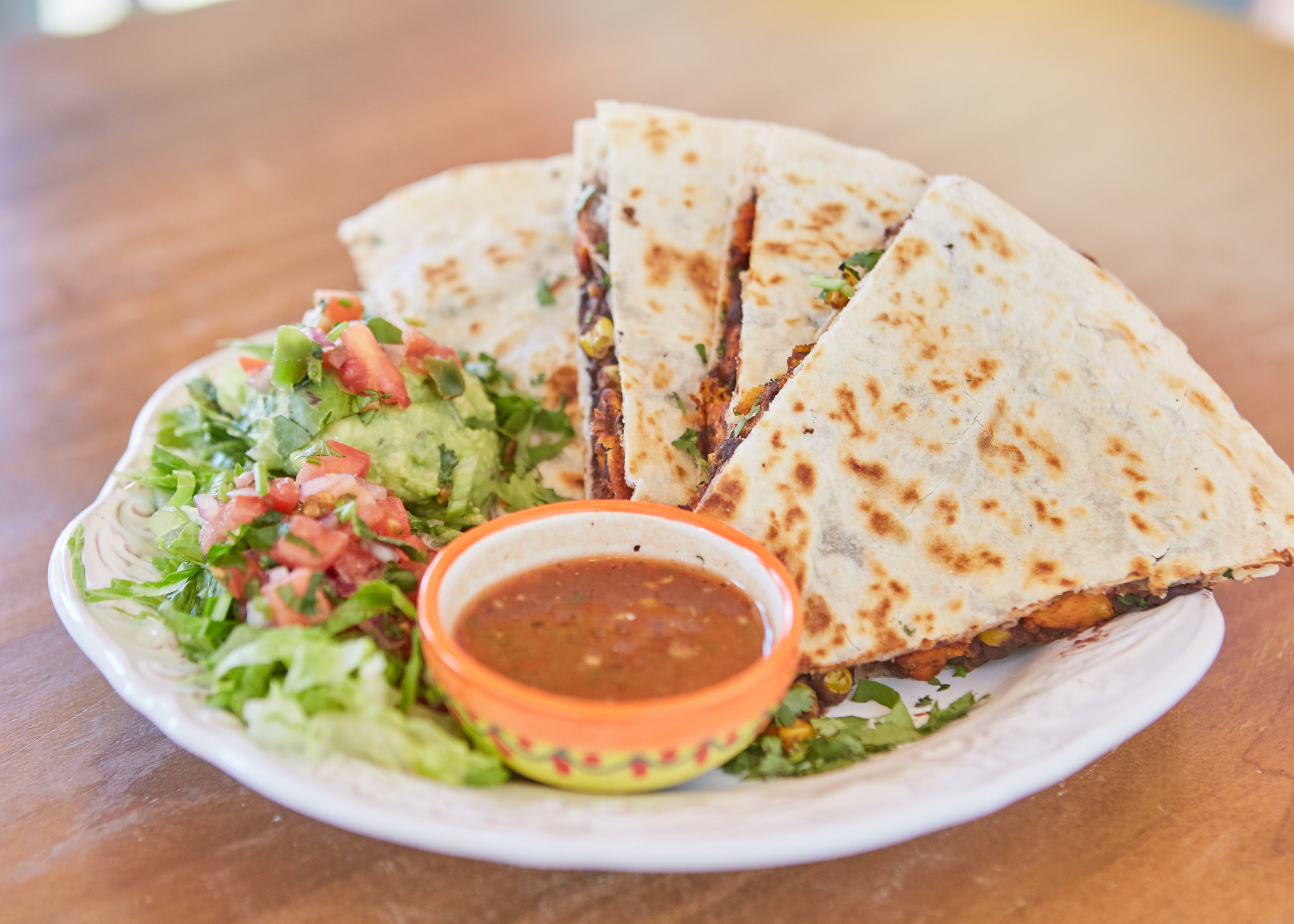 QUESADILLAS $8.99 - SPICY CHICKEN Roasted corn, cilantro, chipotle cremaBEEF OR CHICKEN FAJITA Citrus-marinated beef or chicken, plain or dribbled with citrus habaneroSPINACH & BLACK BEAN (V) Black beans, spinach, roasted corn, poblanos, red bell peppers and zucchini (Veggie)SWEET POTATOES & BLACK BEAN (VEGAN) No cheese –– Black bean spread, sweet potatoes, roasted corn and cilantro topped with guajillo-tamarind drizzle