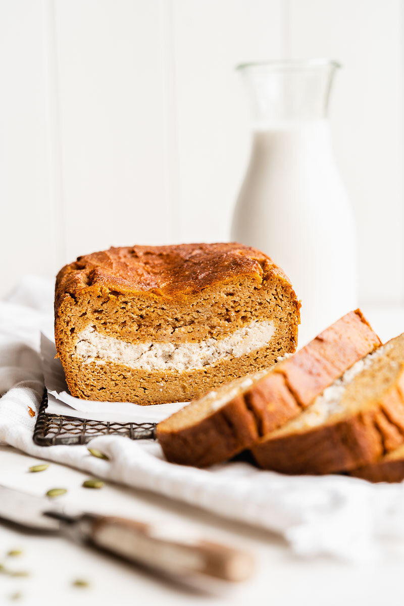Paleo Pumpkin Bread - The Fit Peach   Extra fluffy pumpkin bread loaded with a vegan cream cheese filling — it's the ultimate fall baked good with a healthy twist! Made with natural ingredients like almond flour, REAL pumpkin, coconut milk, and more, it's full of cozy flavors and super simple to whip up.