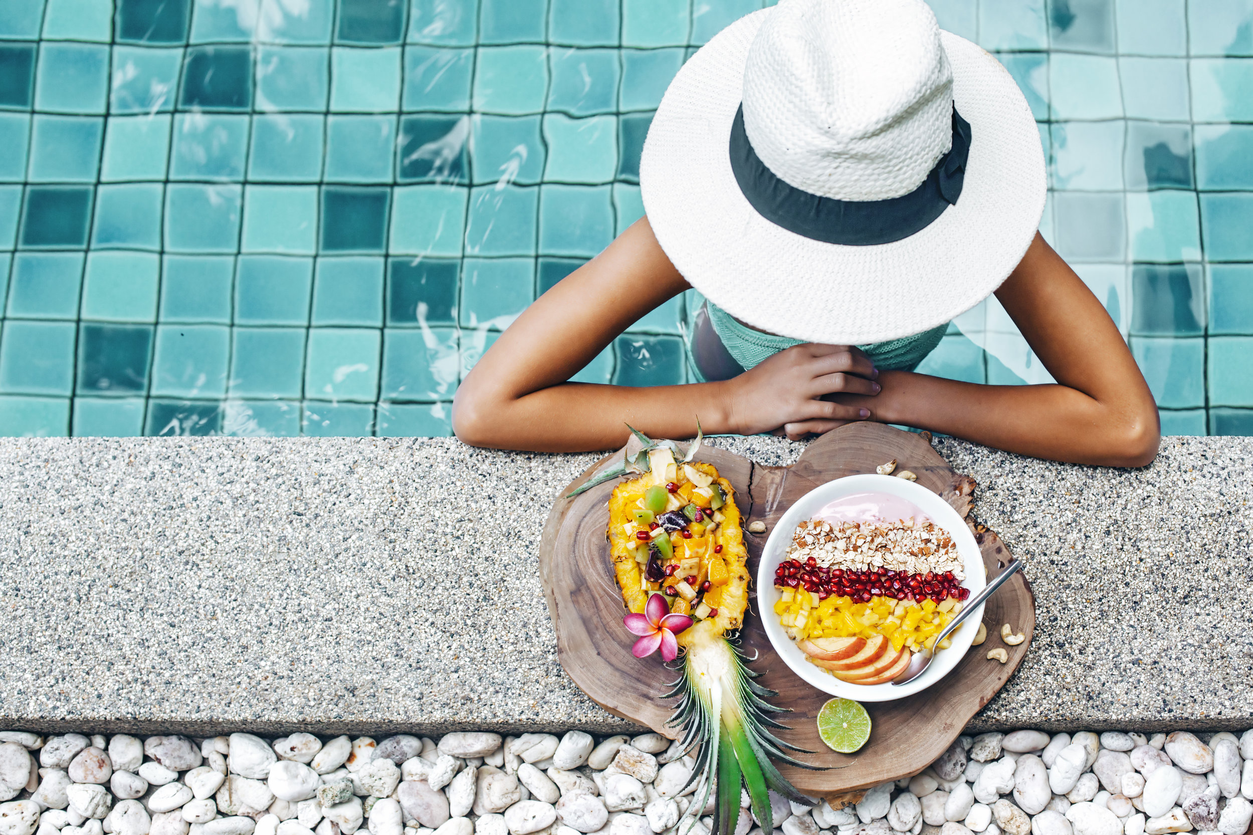 pineapple and woman by pool with white hat.jpeg