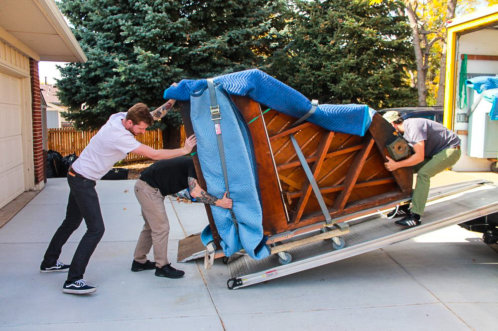 Seattle piano moving crew loading a grand piano on dolly into truck with a loading ramp
