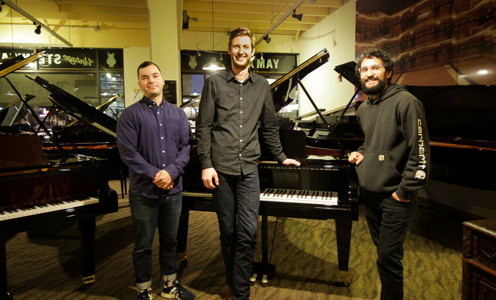 A photo of three members of the seattle piano moving team in front of a black bosendorfer grand piano and surrounded by several other grand pianos in a showroom
