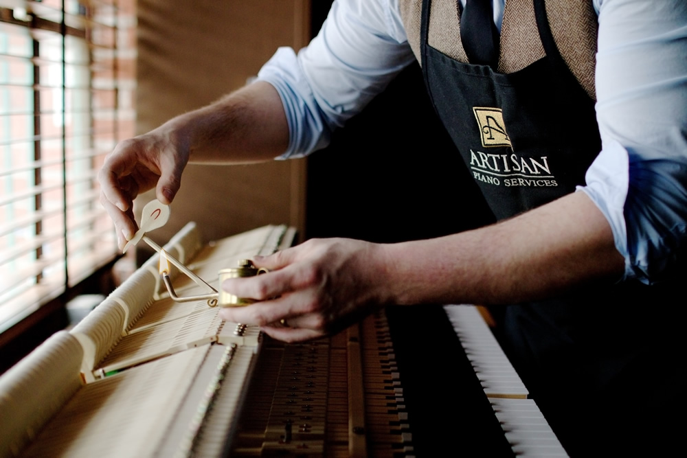 artisan piano technician working with a grand piano action on work bench. the technician wearing a blue dress shirt, vest and apron is applying heat to a grand piano hammer shank in order to to set the hammer in the correct position