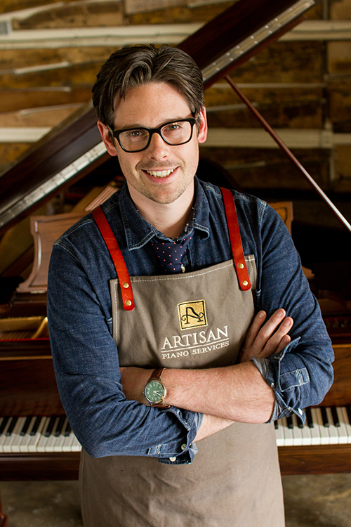 Artisan piano services technician wearing shop apron with red straps and artisan piano services logo. behind the technician there is a steinway grand piano with the lid open. the piano is a mediam brown mahogany with nickel plated hardware