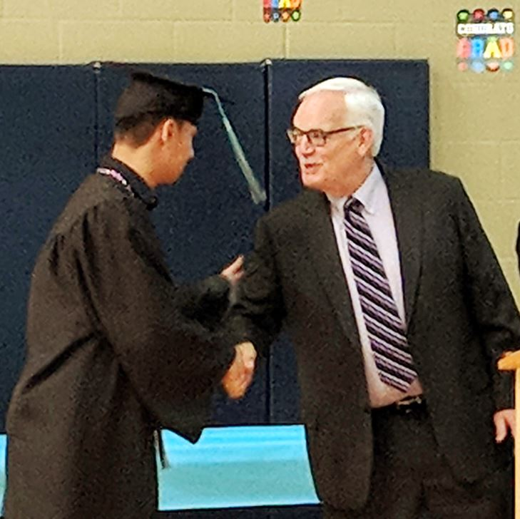 Photo of Bob shaking hands with a Menlo student at graduation.