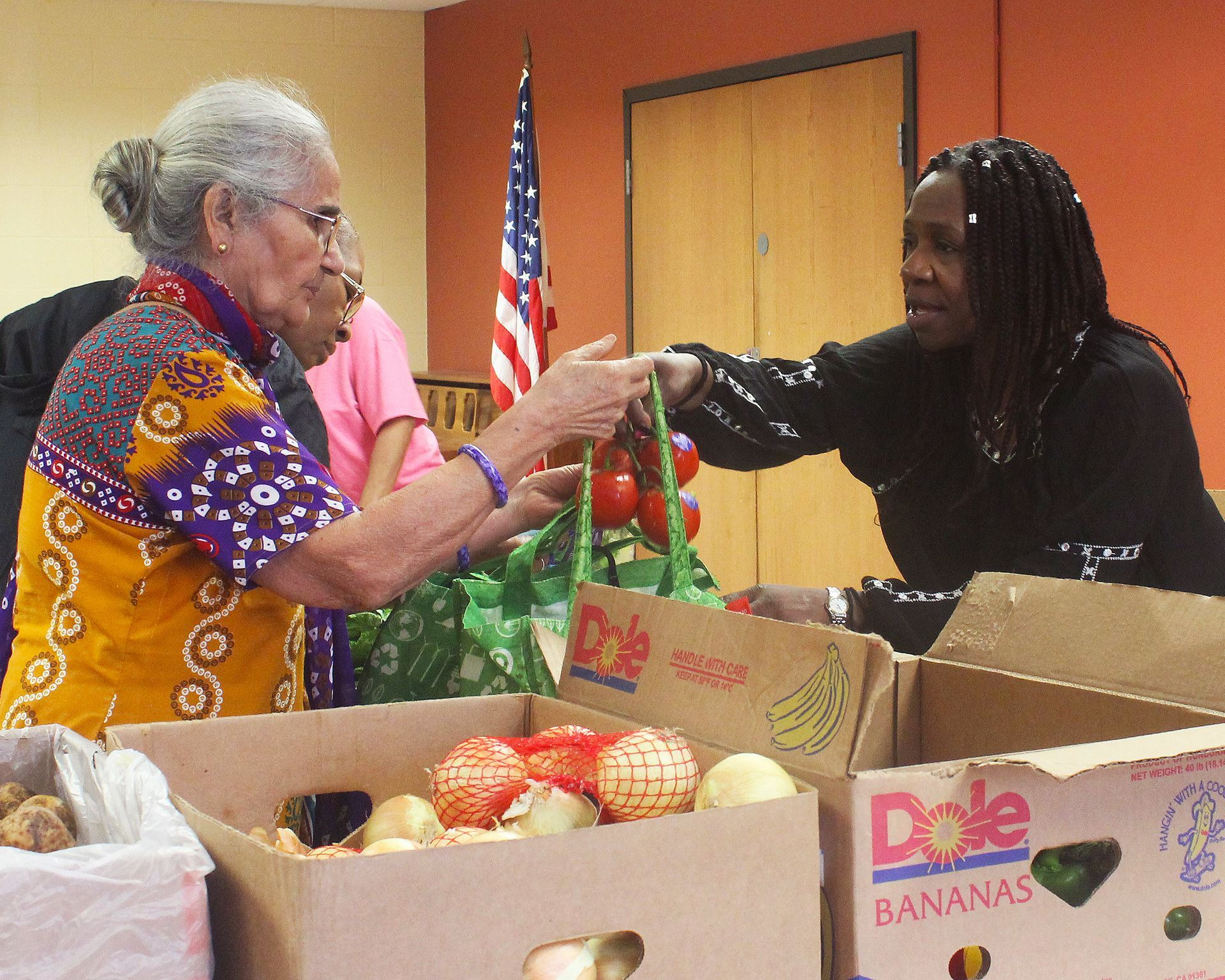 A volunteer handing produce to a client at a High Rise Mobile Food Shelf.