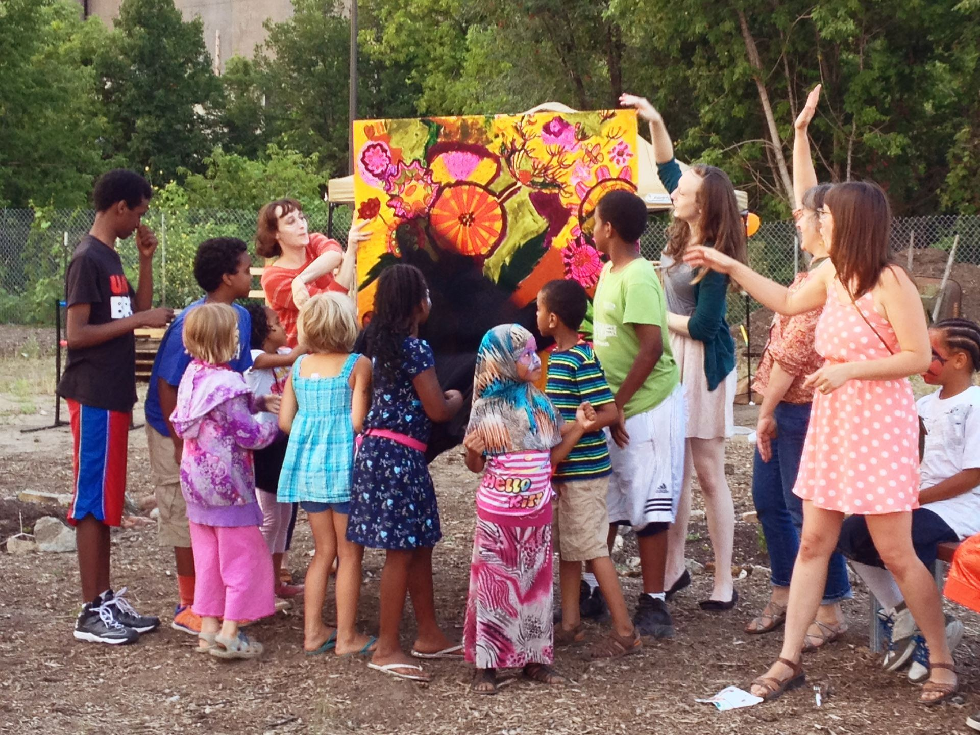 Photo of a group of youth surrounding and looking at a large colorful painting outdoors.