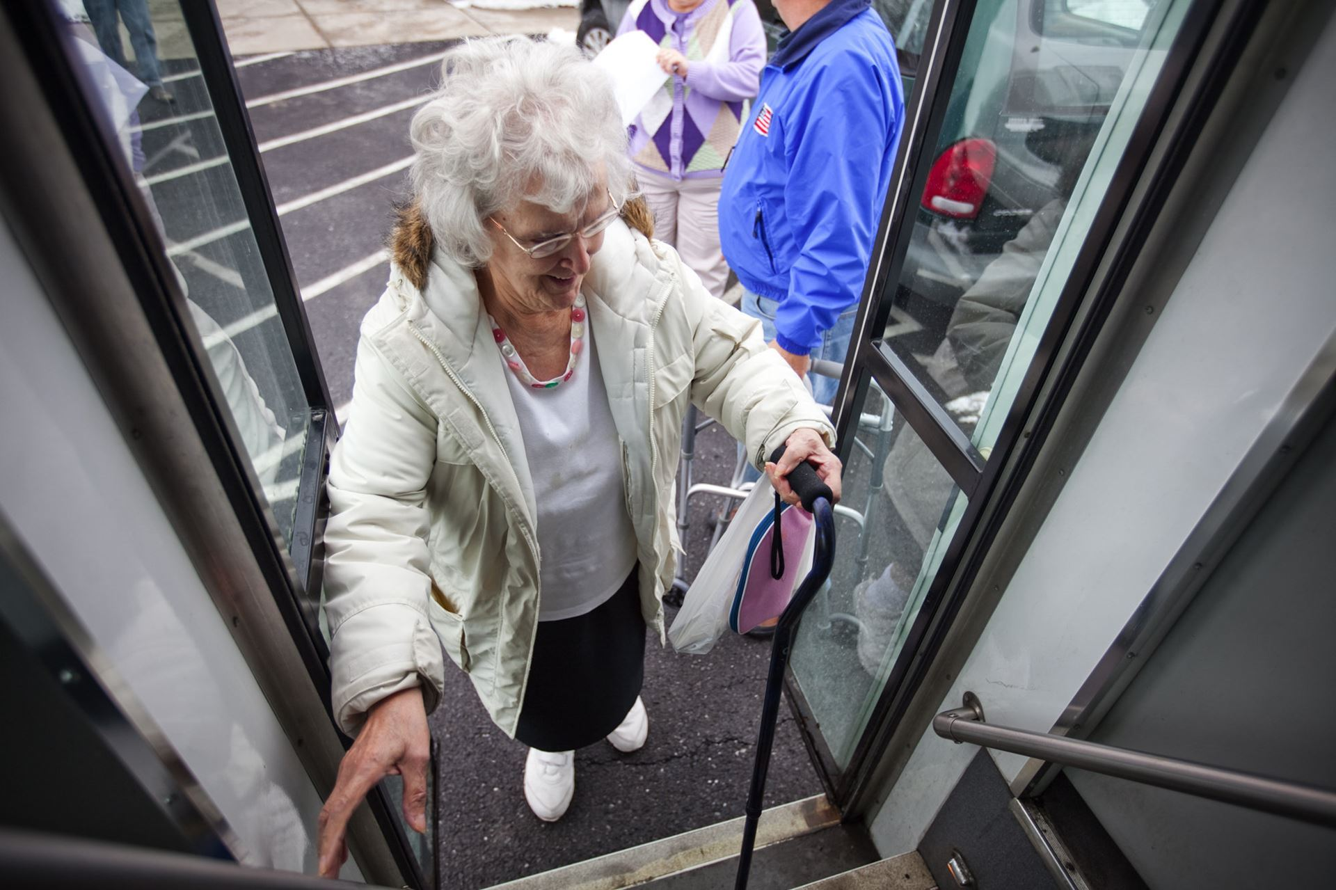 Photo of older adult who uses a cane stepping onto a bus.