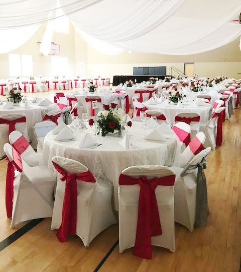Photo of the ESNS gym decorated for a wedding, with white drapery and numbered tables.