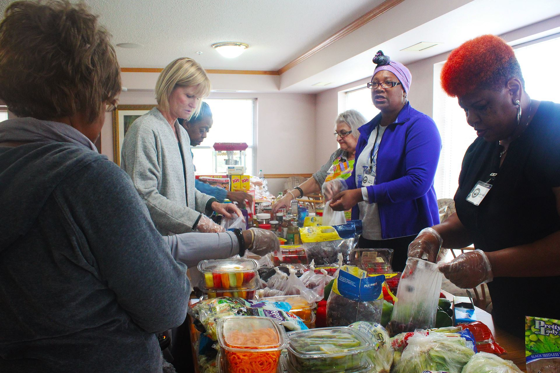 Photo of Kristine Martin and other volunteer distributing produce at a food shelf.