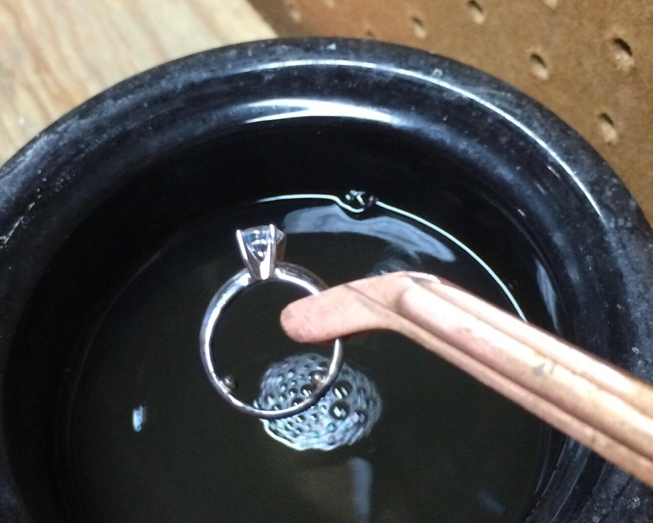 Using copper tongs to prevent contamination, the ring is dipped in an acid pickle bath to remove the black firescale.