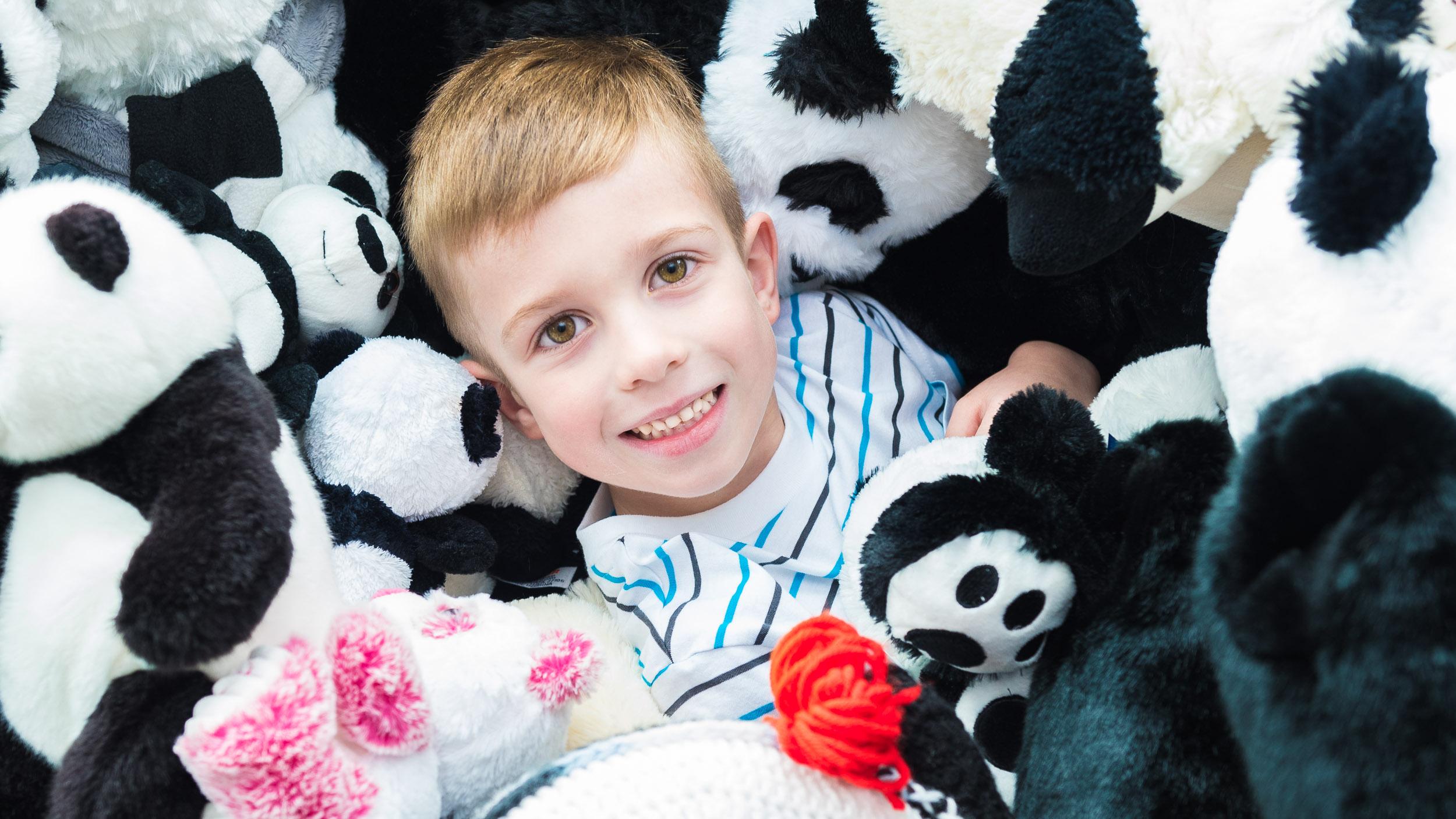 Little-boy-with-stuffed-panda-toys.jpg