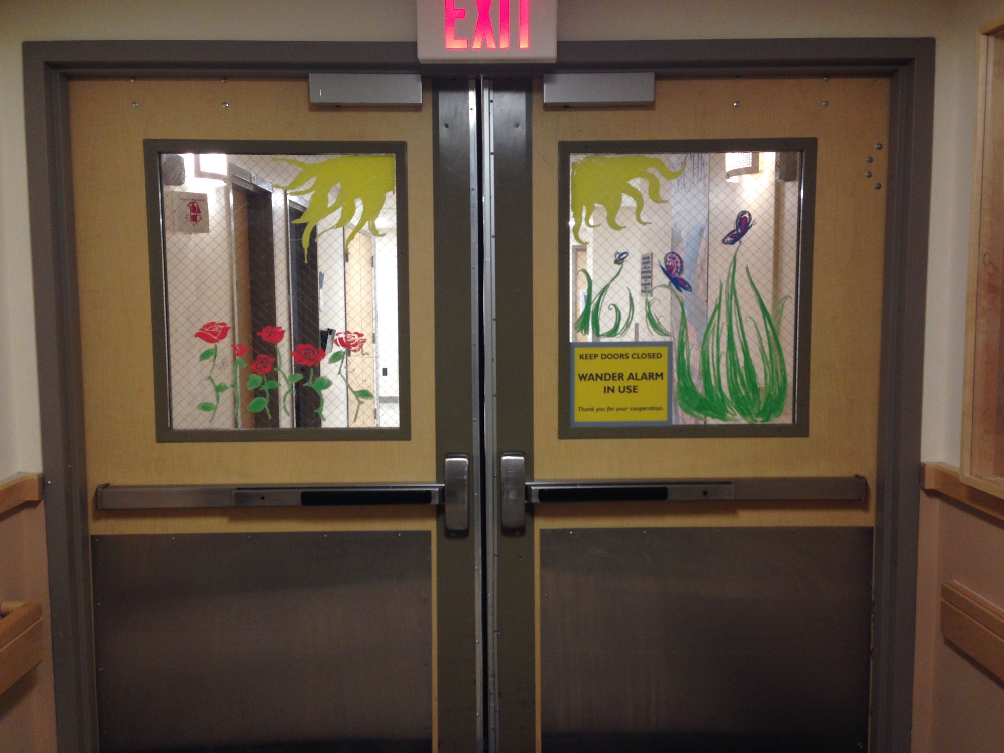 Window drawings by volunteers to help greet people at the entrance to a hospital unit.