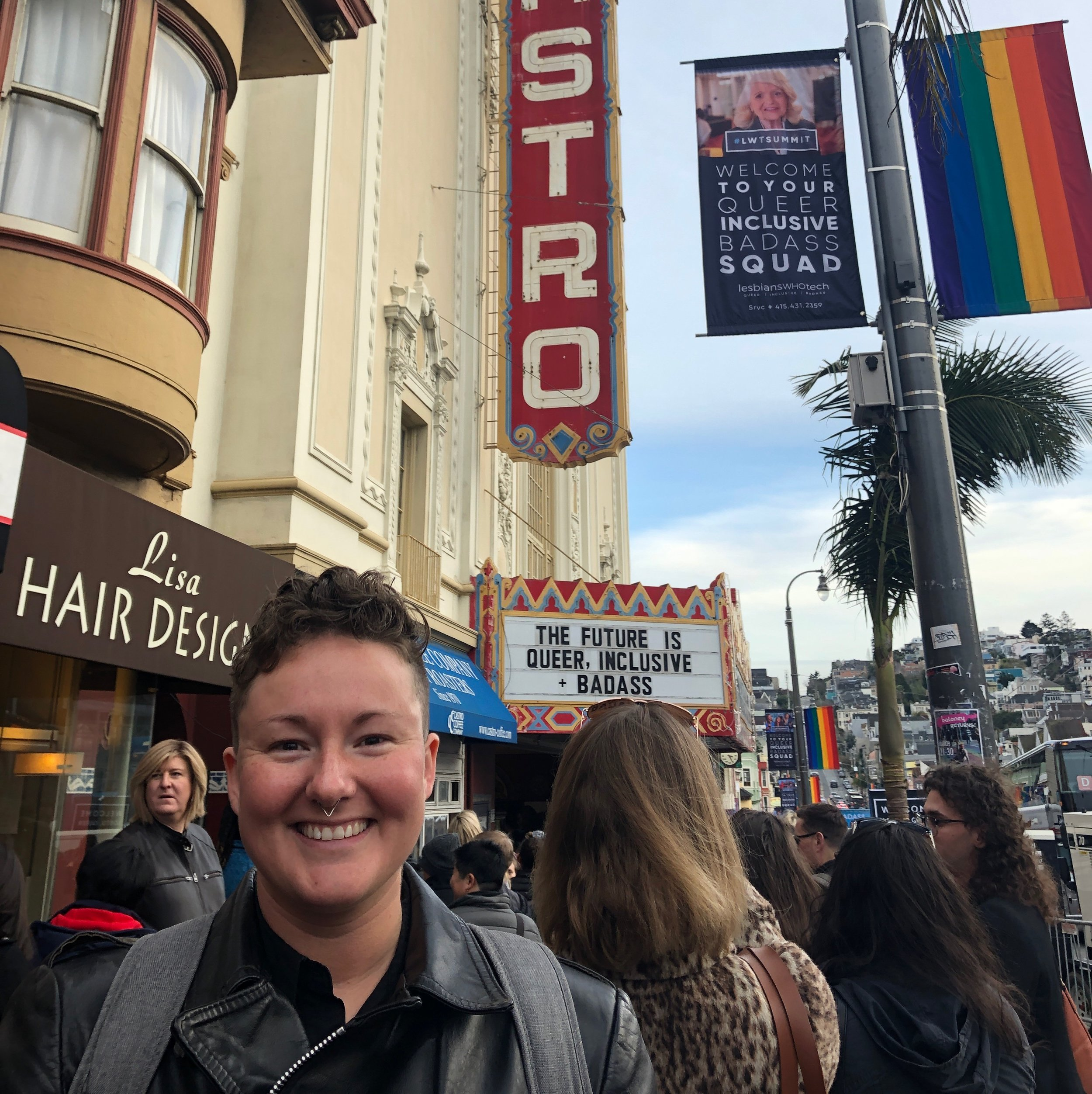 """RC standing in front of the Castro Theatre. The Castro's billboard reads: """"The Future is Queer, Inclusive, Badass."""""""