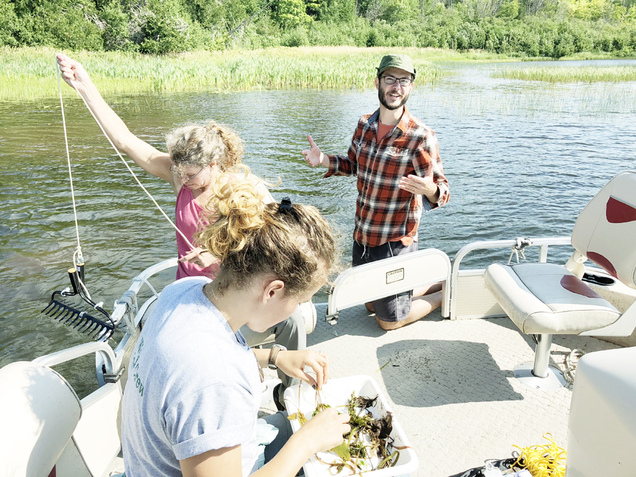 "Pictured above are Erick Elgin (at right) and Keweenaw Invasive Species Management Area (KISMA) Coordinator Sigrid Resh and members of the KISMA weed crew sampling aquatic vegetation with a ""weed rake"" at Gratiot Lake during the EAPW training."