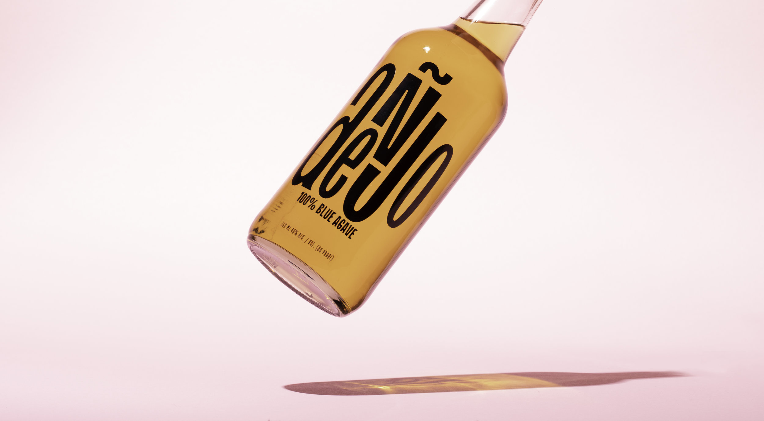 Anejo Tequila Bottle Floating in Air above pink Background