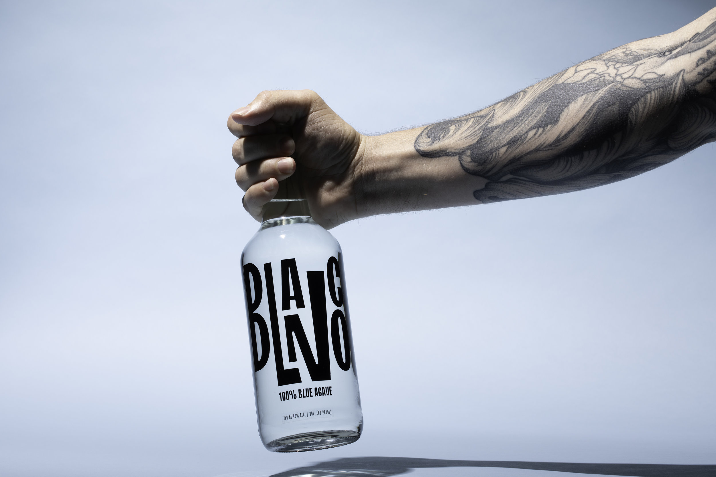 Blanco Tequila Bottle In hand with tattoo