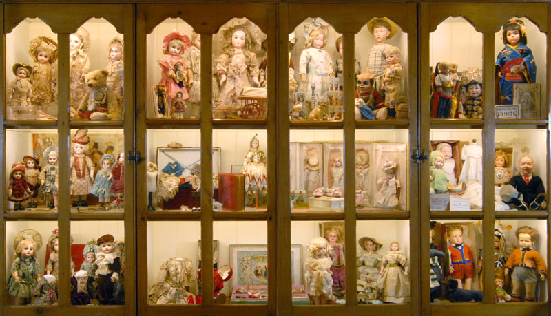 """This cabinet in The Gold Room contains the """"Beautiful Children"""" exhibit via  The Grovian Doll Museum"""