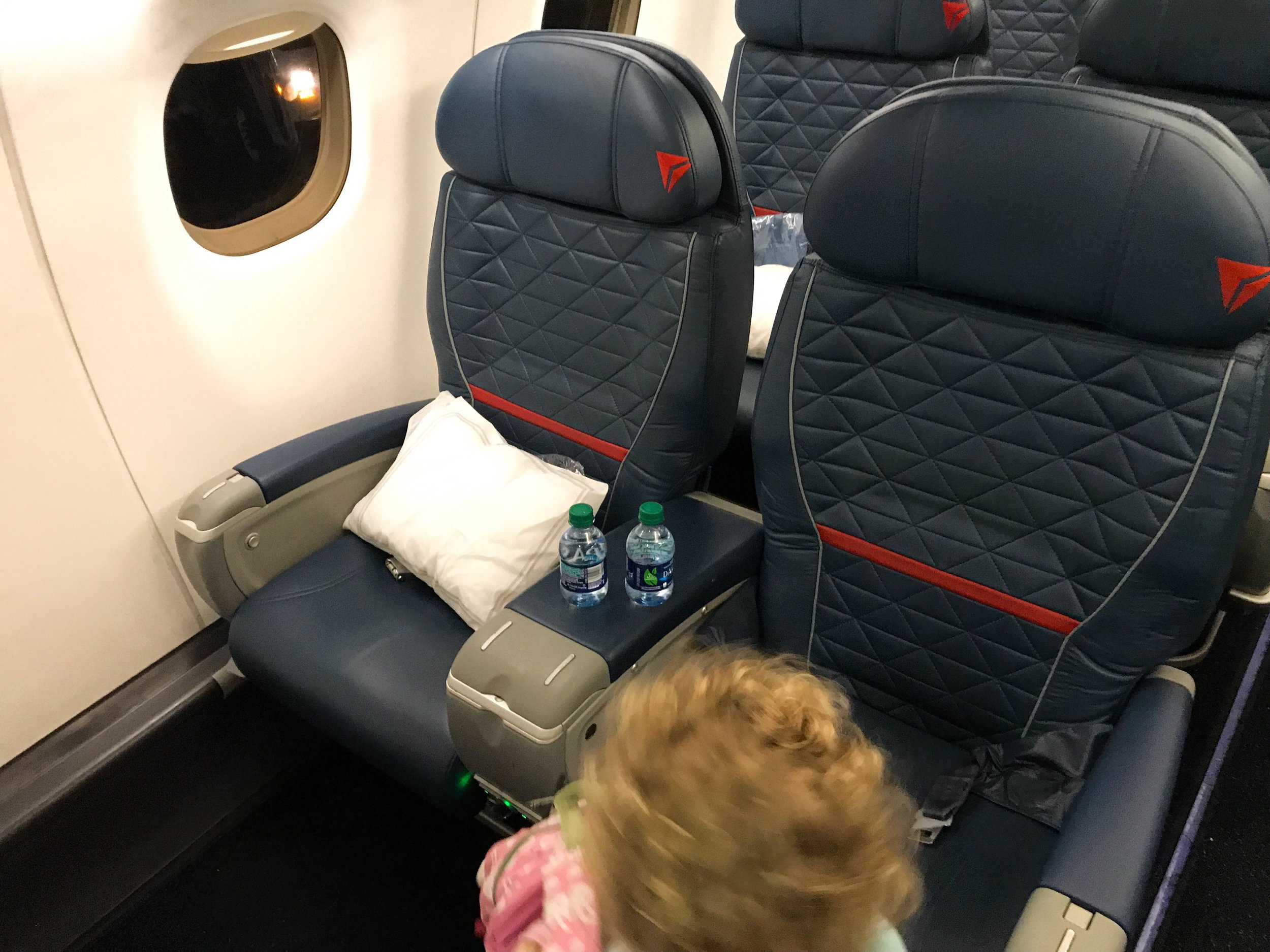 Delta boards families traveling with small children right after passengers needing extra assistance. This is usually reserved for families with children under two and with strollers, but the gate agents graciously told me we could board with this group (I wasn't even going to try).