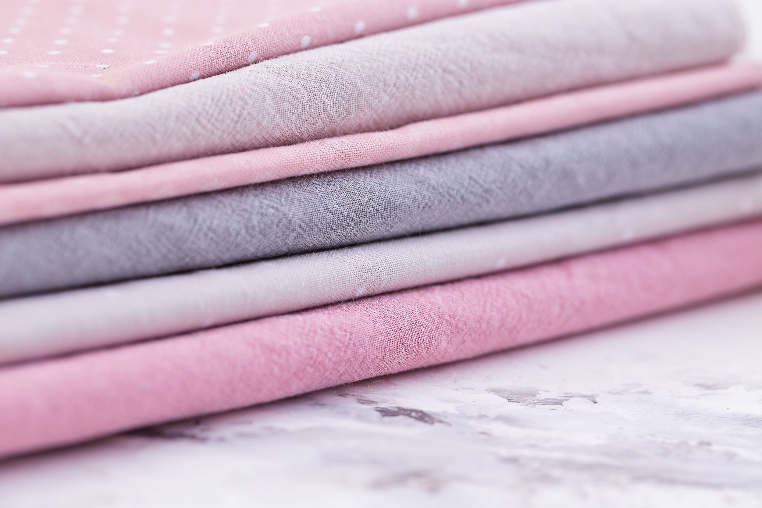 stack-of-fabrics-over-marble-table-PQRAF8Z.jpg