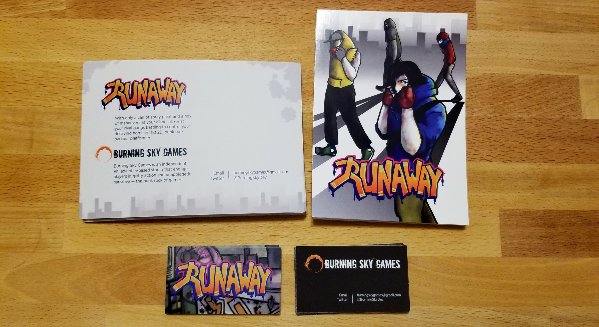 The fronts and backs of the postcards and business cards. All include contact information and Twitter, and the postcards also have a short summary of the game and company. Next time, we'll add our website link too.