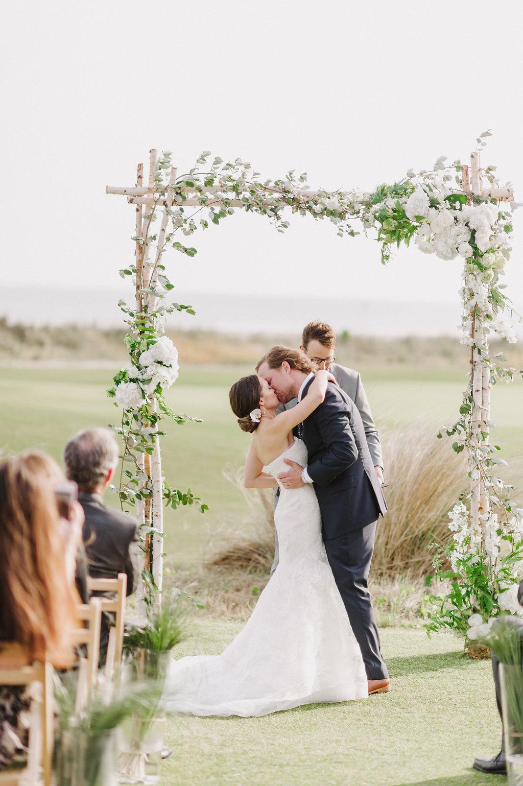 Wedding by the sea, Events by Reagan, Kiawah Wedding, Charleston Wedding Planner, Wedding Ceremony, Bride and Groom Kiss,  Flower Arch