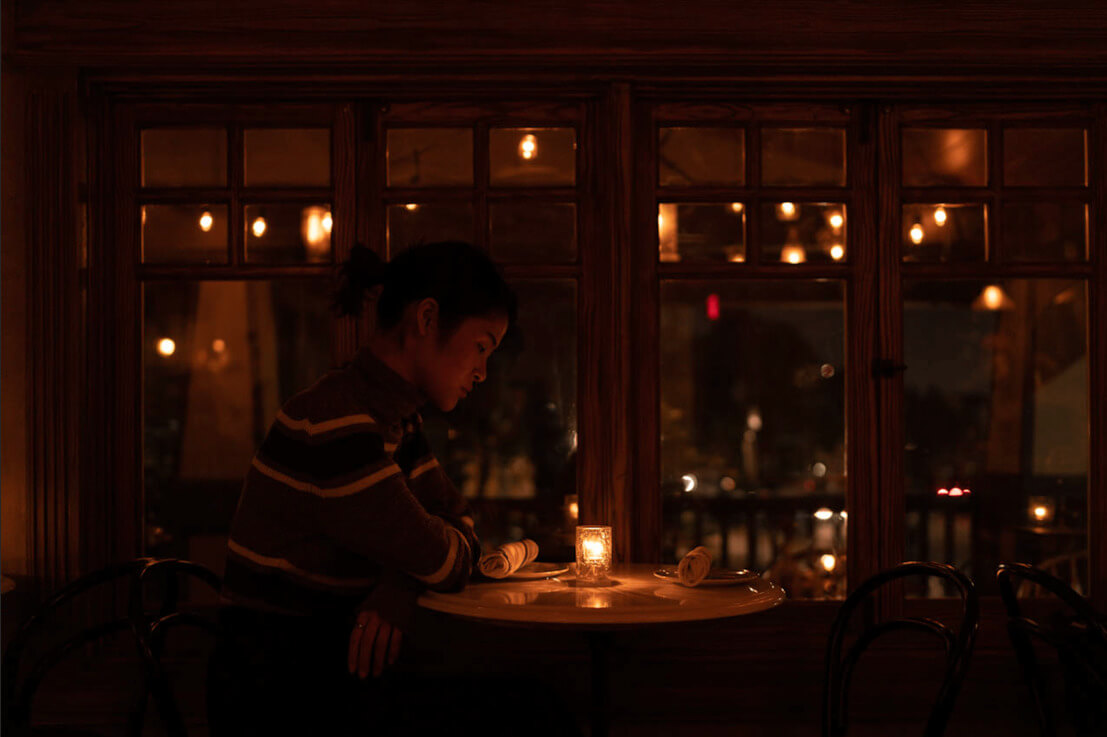 Initial exploration - girl sitting in a cafe; candle to set the mood and atmosphere, soft lighting, windows in the background to frame this photograph.