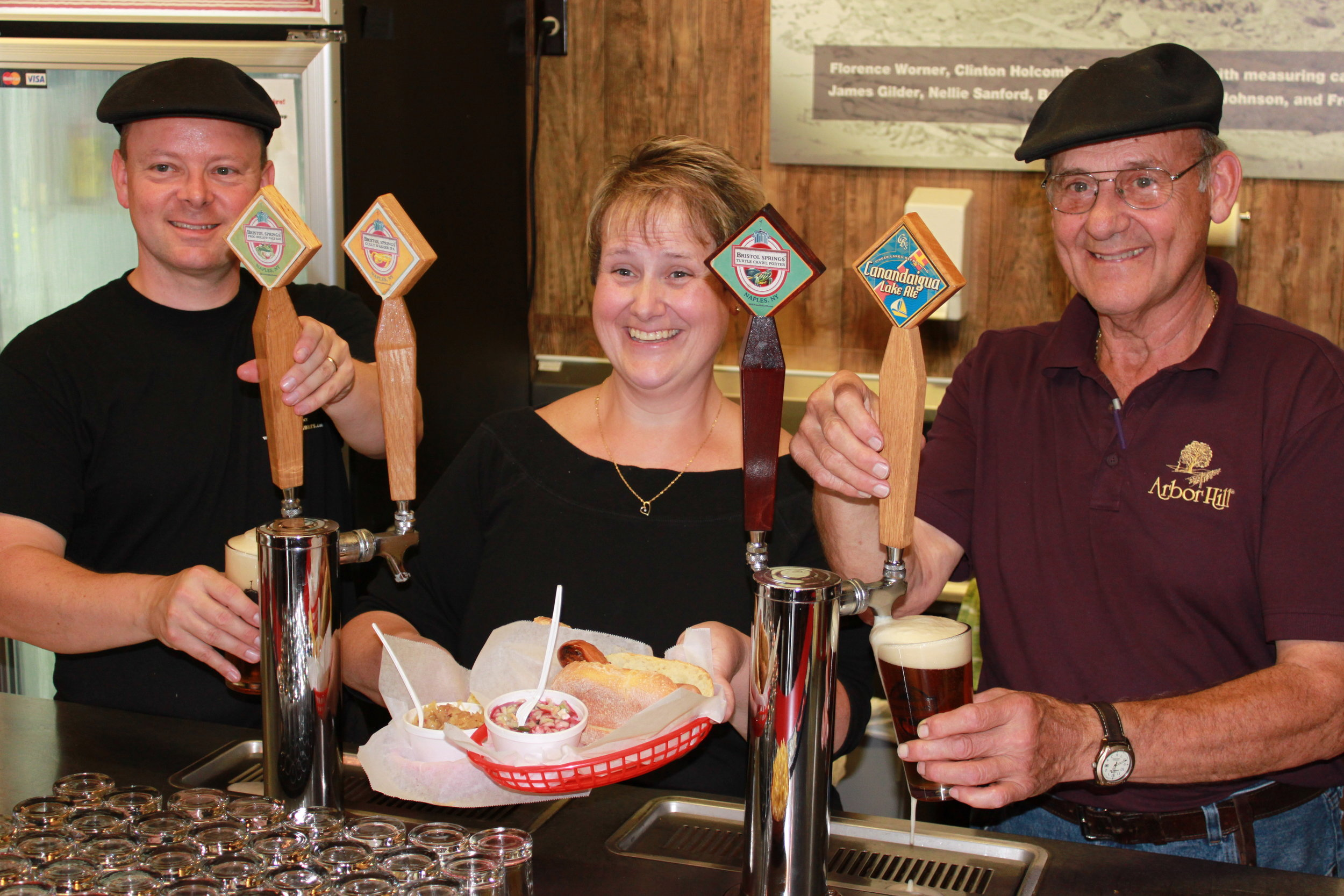 John French, Sherry Brahm-French and John Brahm behind the bar at Brew and Brats at Arbor Hill.