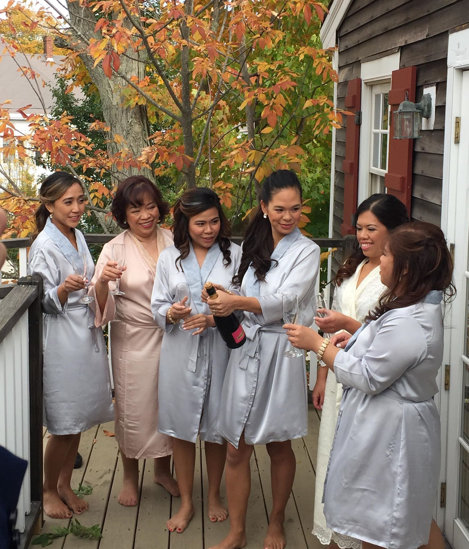 Fall bridal party popping champagne