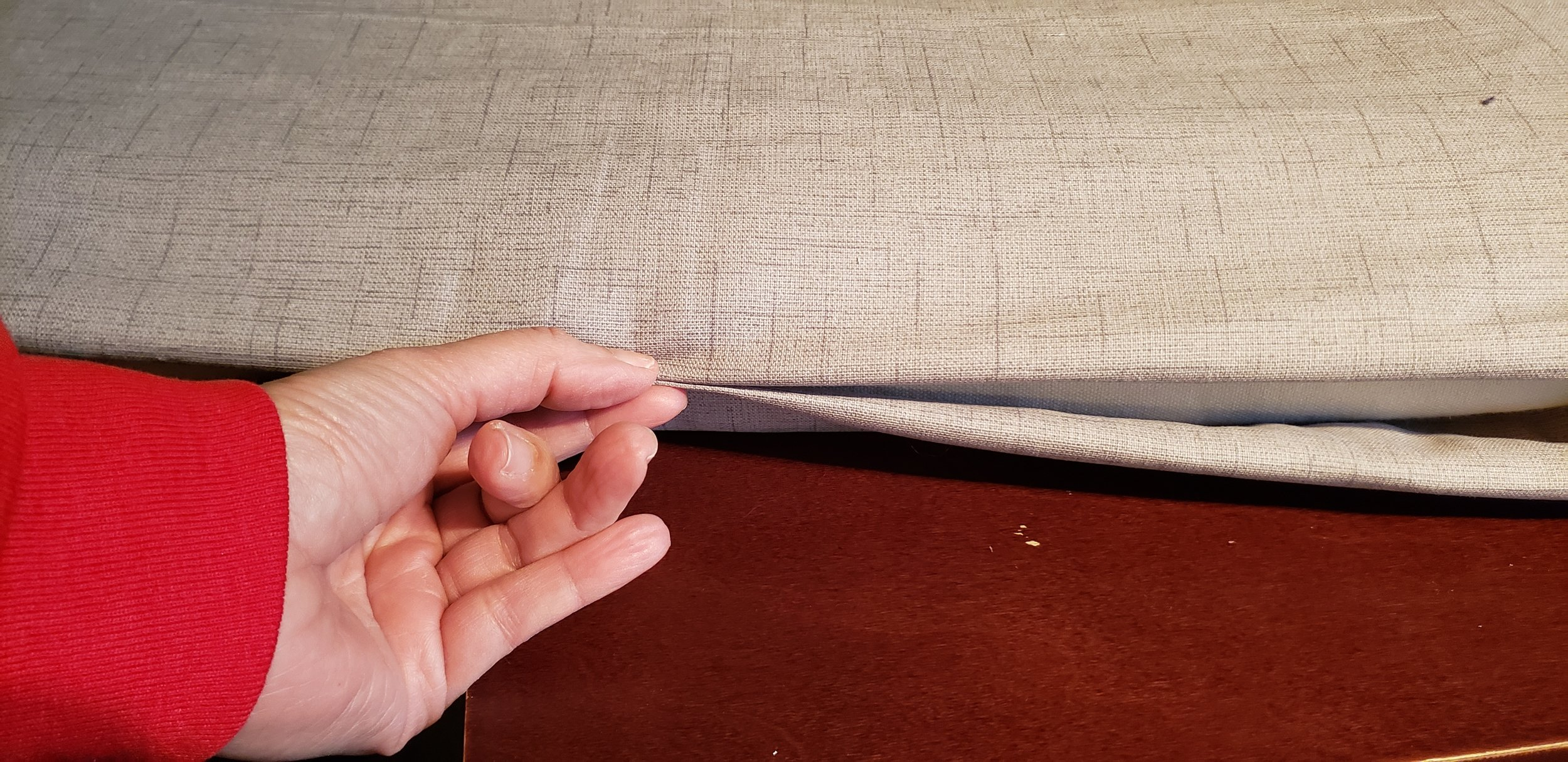 - I started by tucking under the fabric to create a hem and leaving only enough room for a zipper to close (using a pinch of my fingers as my guide for how much room to leave). My thumb is touching the end of the cushion that is inside.