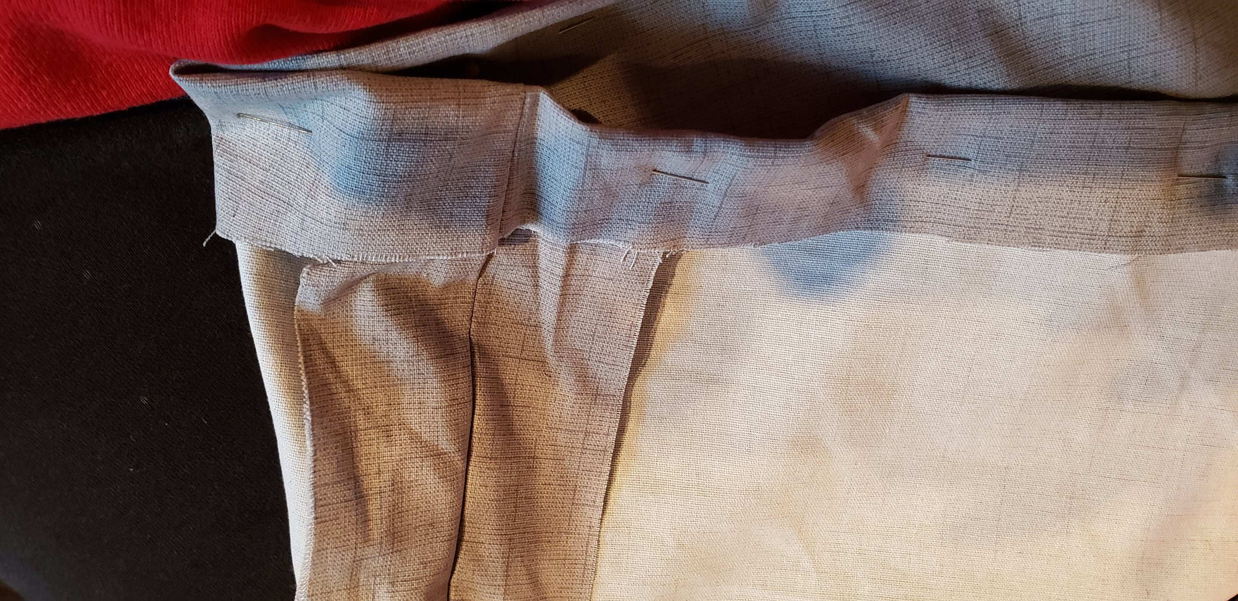 - I removed the cushion with the pinned hem, turned the fabric inside out, and ensured that any seam on the inside would be flattened so that the hem would be sewn over the seam appropriately for best results.