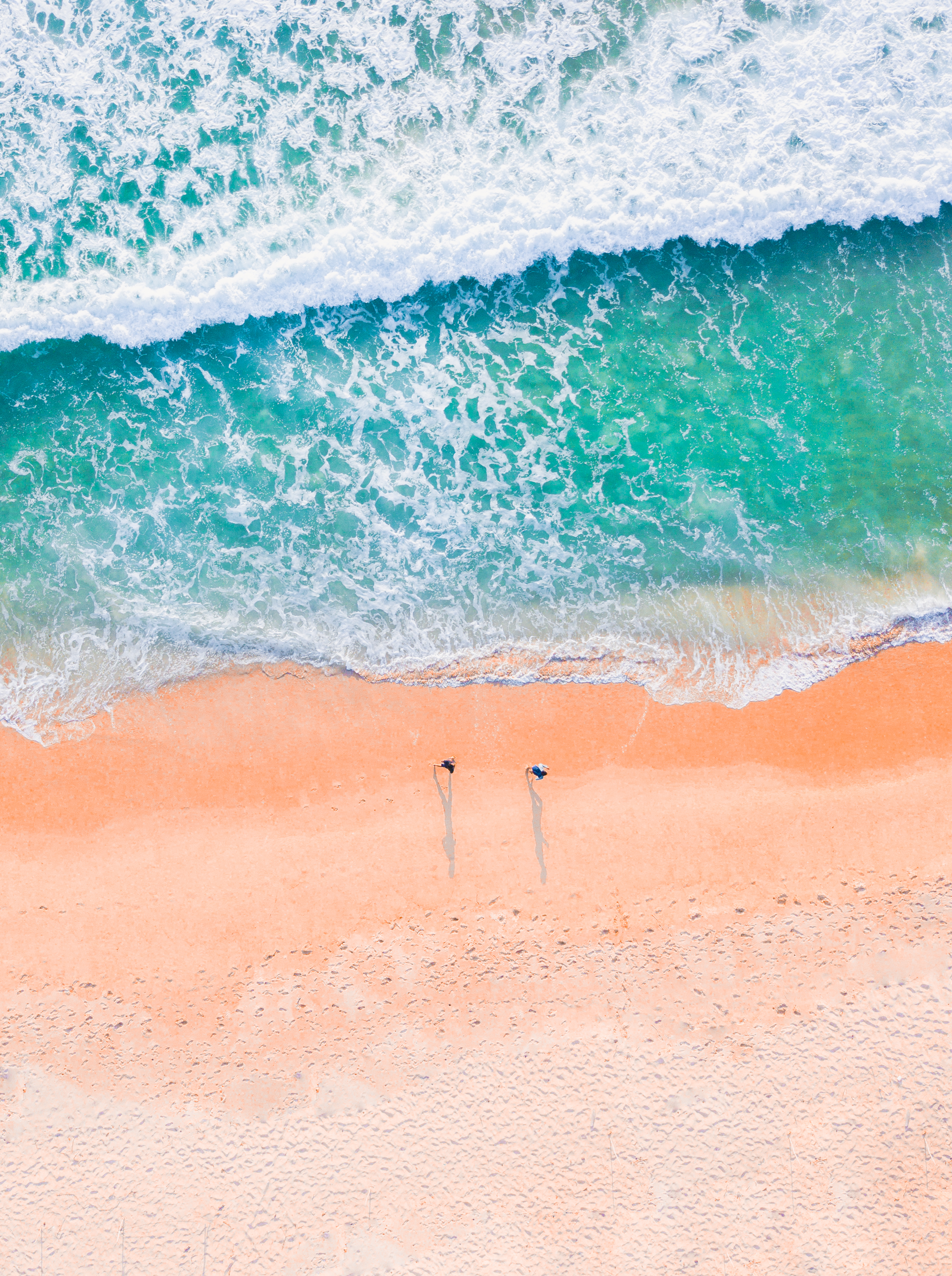 aerial photo of two people on a sandy beach