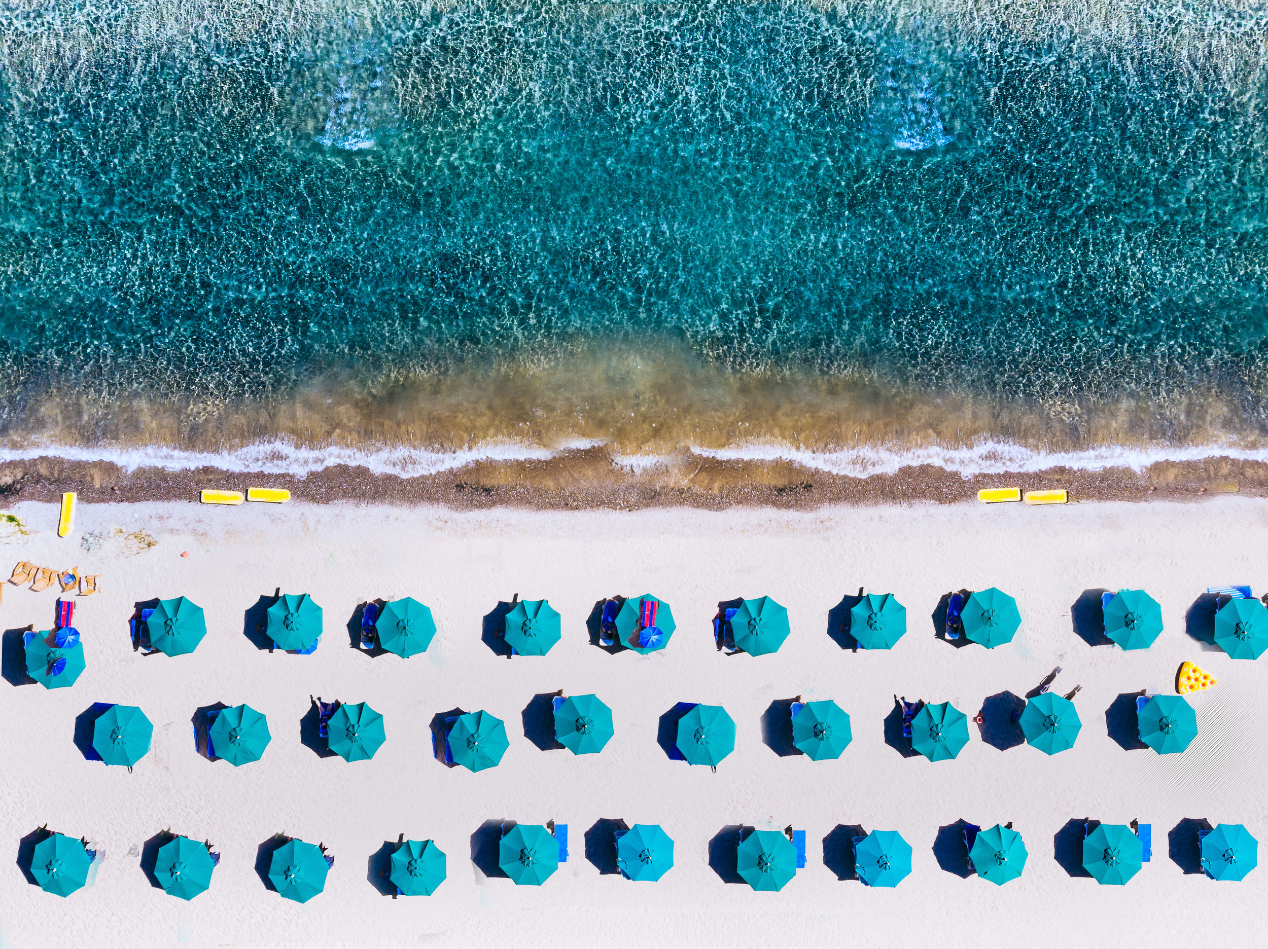 Beach lined with blue umbrellas