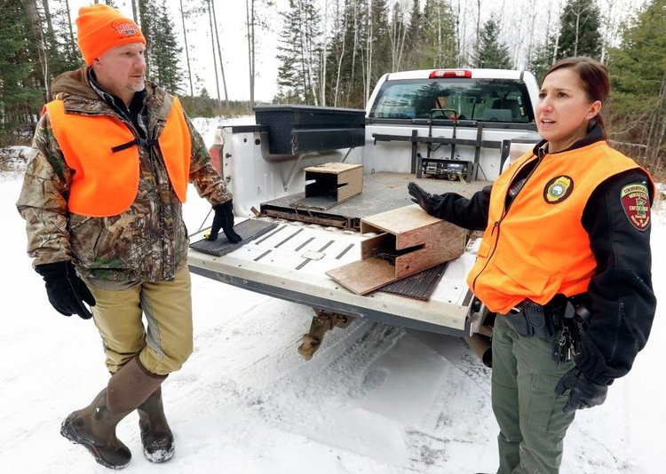 Minnesota conservation officer Kipp Duncan listens as officer-in-training Leah Kampa talk about two fisher/martin trapping sets they confiscated for violations of state law. Steve Kuchera / Forum News Service