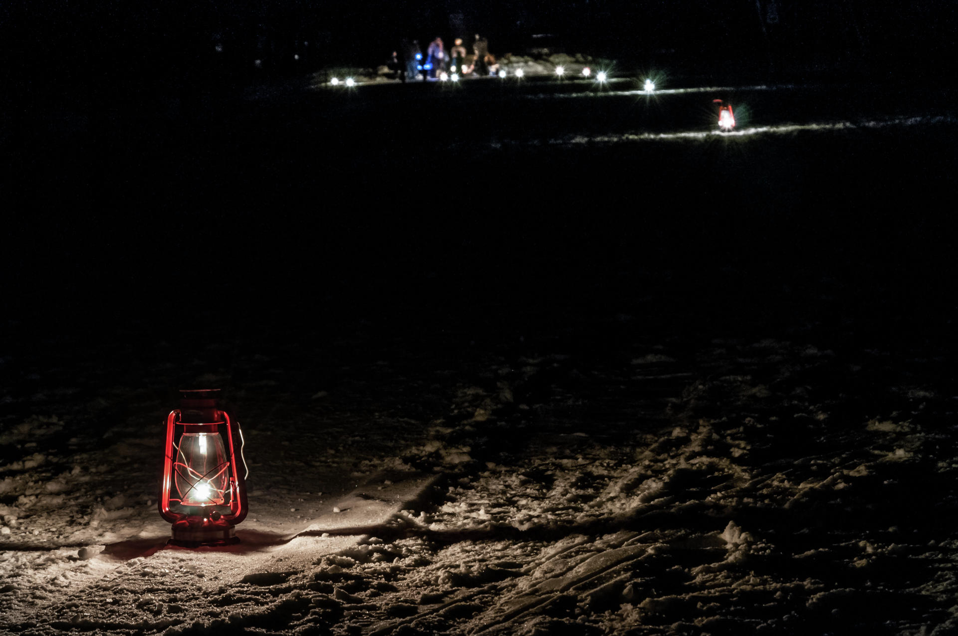 A single kerosene lantern lights this portion of the Lantern-Lit Ski & Snowshoe trail at Itasca State Park, as a campfire crackles merrily in the distance. (Minnesota DNR photo)
