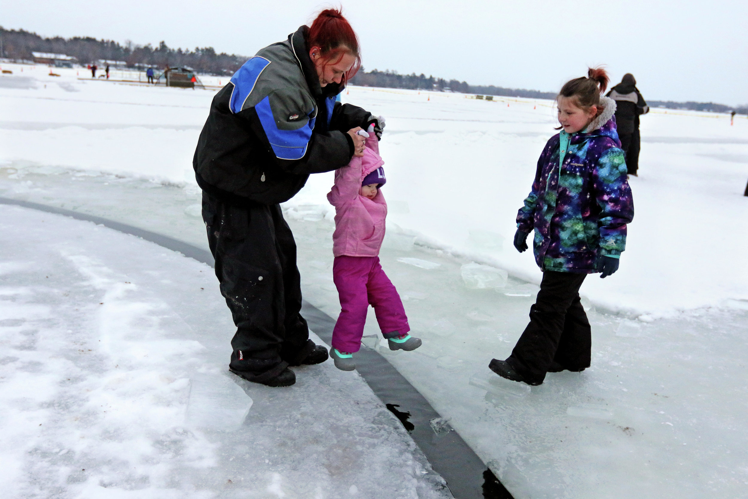 Annmarie Lyon assists daughter Paisley Lyon off of the spinning ice carousel with the help of daughter Zoë Lyon on the other side Saturday, Jan. 12, during the second annual Sunny Zwilling Memorial Ice Carousel Extravaganza in Little Falls. Kelly Humphrey / Forum News Service